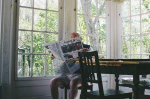 elderly man reading news